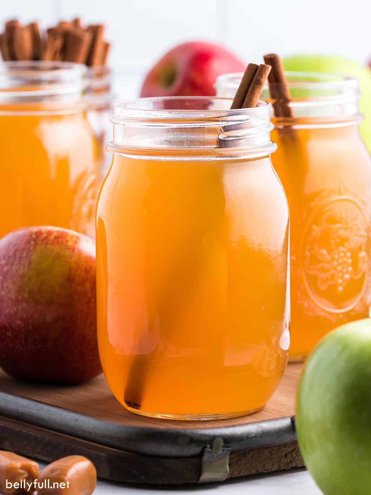 Mason jars of homemade apple pie moonshine garnished with a cinnamon stick