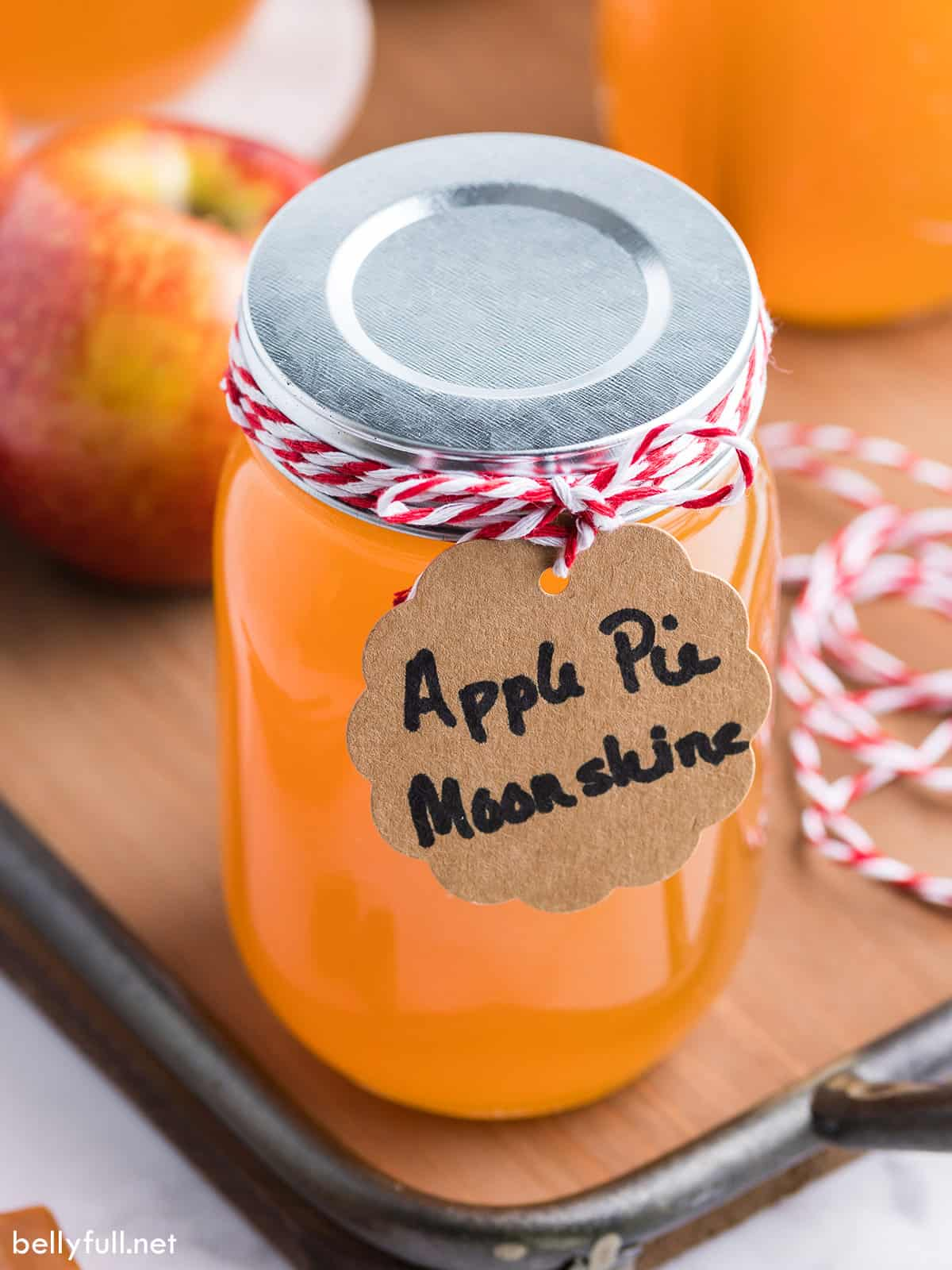 A mason jar of apple pie moonshine with a ribbon for gift-giving