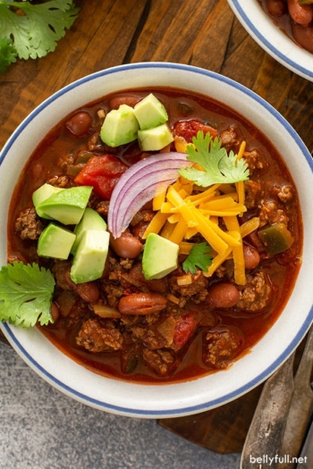 overhead bowl of chili with cubed avocado and shredded cheddar cheese